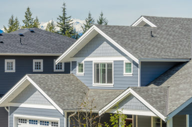A residential roofing system on a blue suburban home