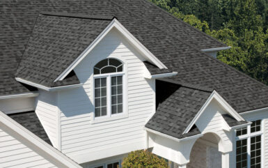 A gray asphalt shingle roofing system is shown from above on a residential home